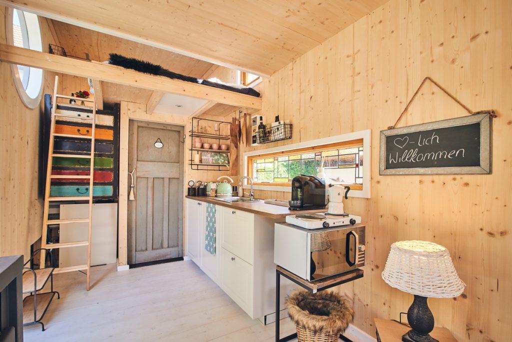 Blick ins Tinyhouse Sauerland Helden. Die Küche rechts, ins Bad gehts gradeaus durch die Tür. Zum schlafen die Stiege nach oben.